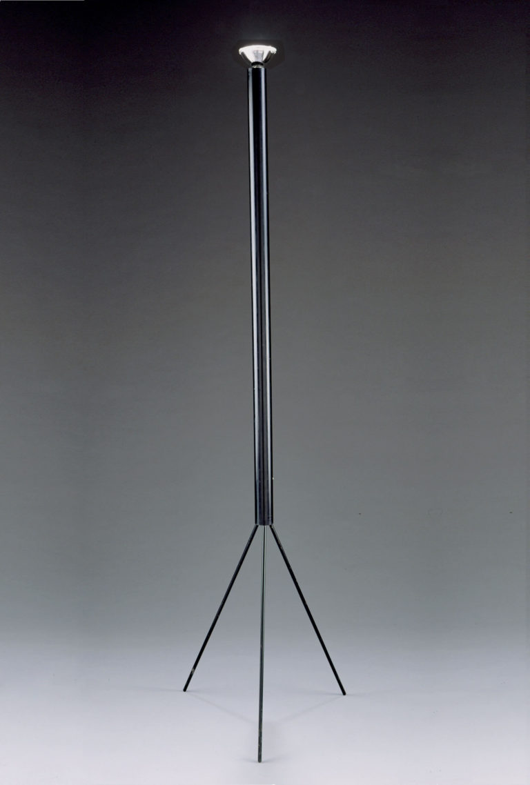 Black floor lamp with a tripod base and long cylindrical stem with a bare halogen bulb at the top.