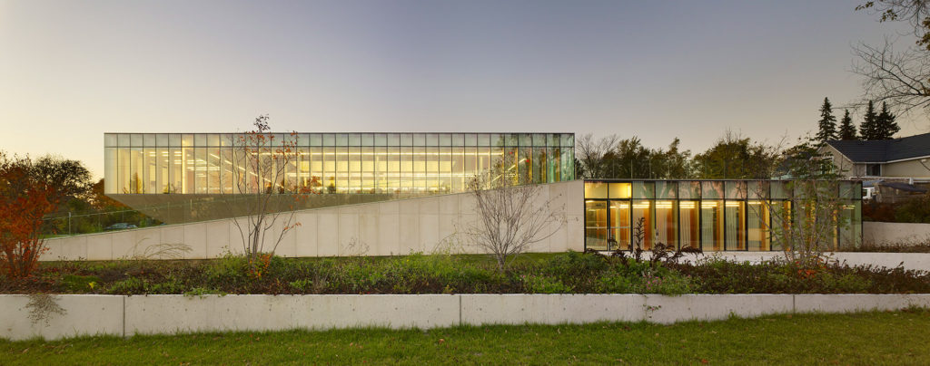 Low rectangular glass building surrounded by slanted limestone retaining walls.