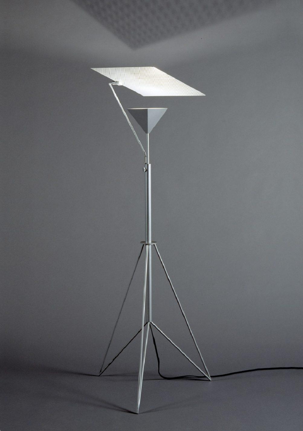 Lampadaire à tige d'aluminium avec trépied à angles et boîtier en pyramide inversée pour l'ampoule, surmonté d'un carré plat réflecteur de lumière.